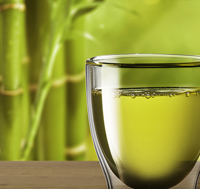 A glass of white tea in front of a bamboo background.